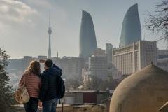 Парень и девушка фотографируют пламенные башни Баку. Азербайджан.